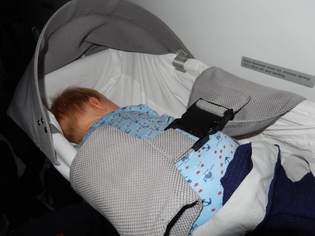 Weltreise mit Baby planen - Quentin als Baby im Jahr 2014 schläft in der Babyschalteauf dem Flug nach Hong Kong