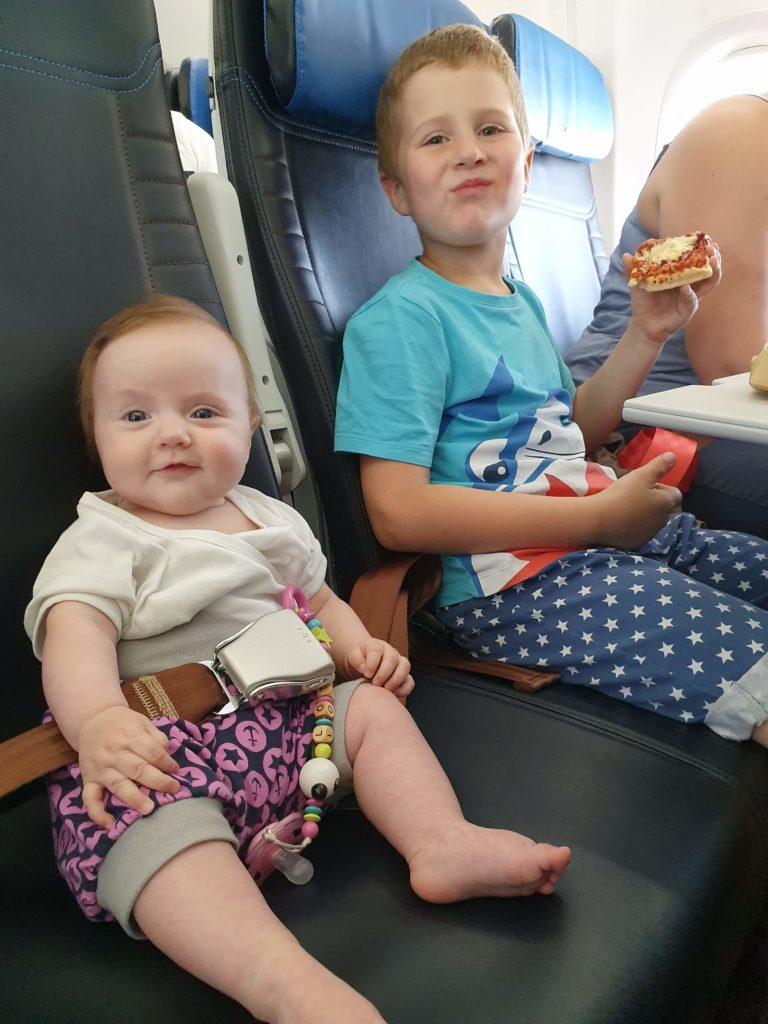 Weltreise mit Baby planen - Baby Charlotte neben Bruder Quentin im Flugzeug