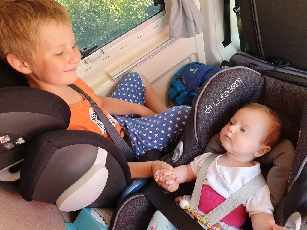 Mit Camper durch Großbritannien - Die Kinder sitzen im Camper und halten ihre Hände
