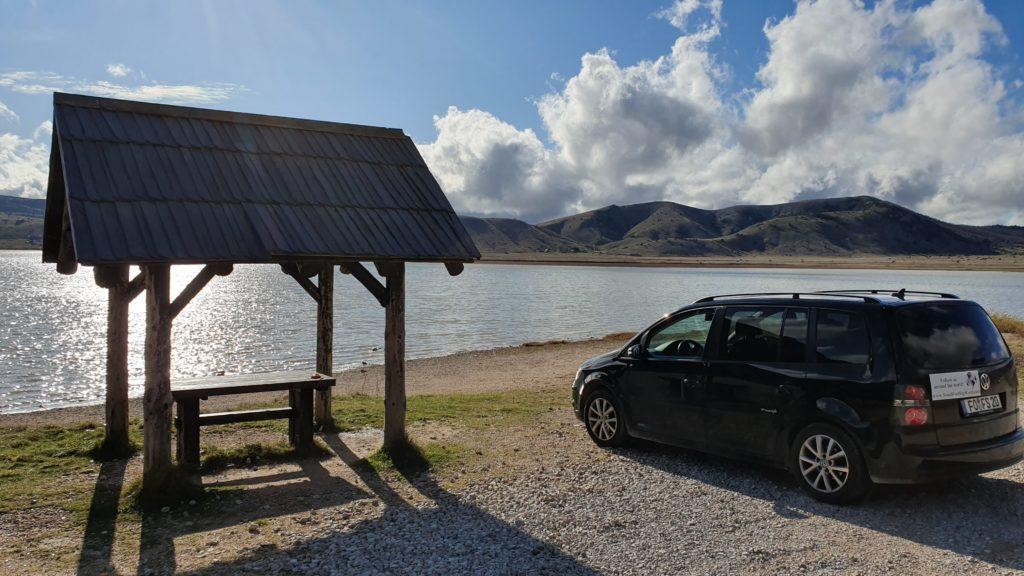 Balkan Roadtrip mit Baby - Auto parkt am Seeufer